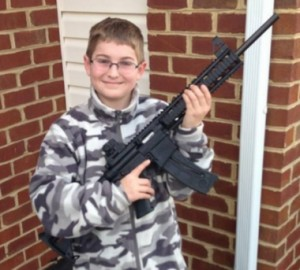 Josh Moore holds the 22-caliber rifle his father gave him for his birthday. The rifle is disguised to look like an automatic assault weapon. Photo courtesy of Facebook.