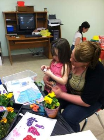 Aunalyese Roberts, 4, paints a picture as she sits on the lap of her mother, Lora Robert in the activity room of the Mercy Center For Women in Erie. Photo courtesy of GoErie.com.