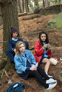 three young people sit on the ground in the forest at the base of a tree